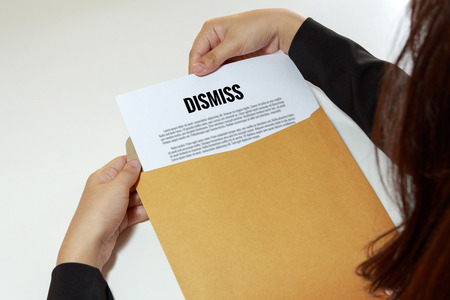 banish: Businesswoman opening the dismiss document in letter envelope - business concept.