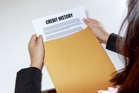 annals: Woman hands holding credit history document in envelope - business concept