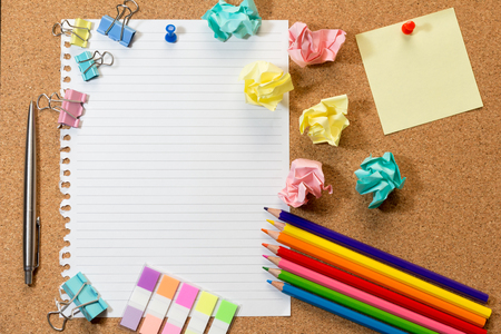 cork sheet: Cork board with blank sheet of paper, colorful blank notes, color pencil, tag, trash and push pins. Stock Photo