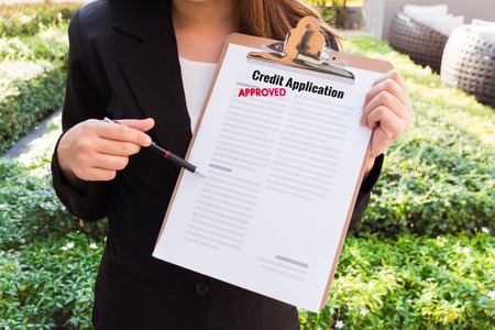 Women in suit showing approved credit application and pointing with a pencil. Stock Photo