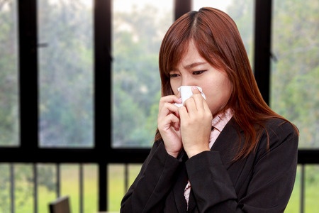Businesswoman with allergy or cold sneezing into napkin in room - health concept Zdjęcie Seryjne