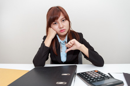 hinder: Unhappy business woman with thumb down in office - calculator, file and document on desk Stock Photo
