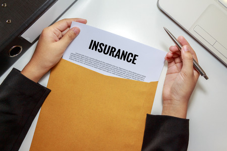 policy document: Businesswoman opening Insurance policy document in letter envelope - business concept.