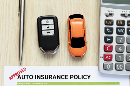Top view of approved auto insurance policy with car key and car toy on wooden desk Imagens