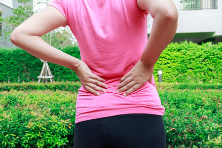 Female athlete lower back painful injury. Sporty woman backache and injury Stock Photo