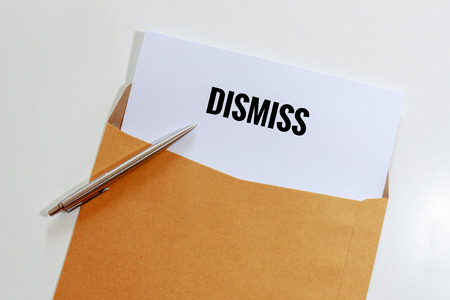 banish: Dismiss document in envelope with pen on table - business concept.