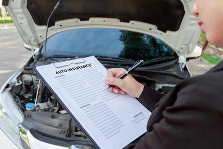 Insurance agent writing on auto insurance document and examining car after accident