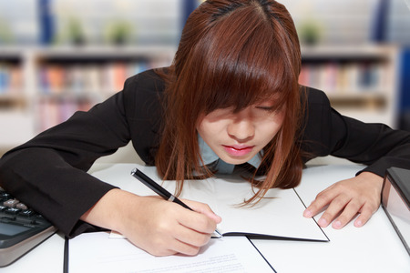Sleepy and tired business woman at desk, holding a pen for writing and close her eyes in library - business concept