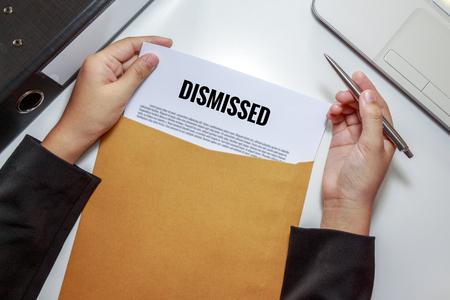 dismissed: Businesswoman opening Dismissed document in letter envelope