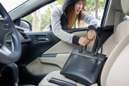malefactor: Woman burglar steal a shoulder bag through the window of car - theft concept