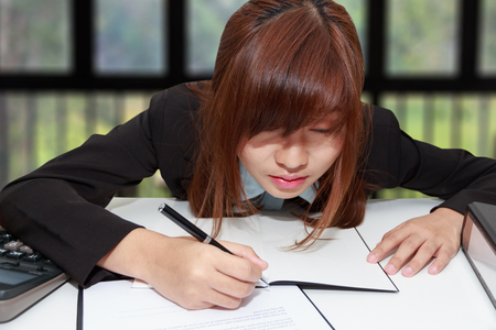 Sleepy and tired business woman at desk, holding a pen for writing and close her eyes in office - business concept