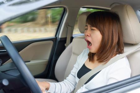 Primer retrato soñoliento, bostezo, cerrar los ojos mujer joven conducía su automóvil después de un disparo una hora de duración, privación del sueño, el concepto de accidente