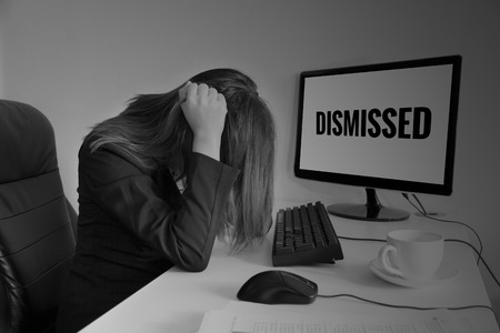 dismissed: Stressed or headache business woman at office desk, dismissed on screen - failure business concept Stock Photo