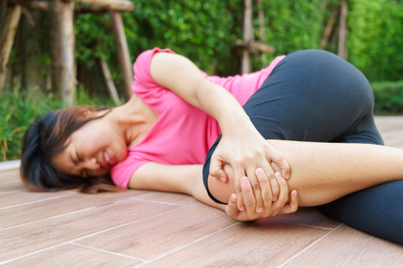 Asian woman runner laying on the floor and touching her injured knee at outdoor - pain concept