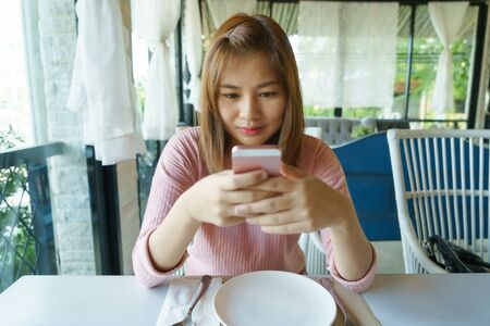 Asian woman using smart phone in restaurant - message, chat or shopping online Stock Photo