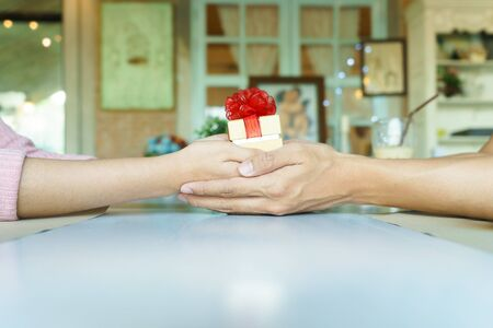 A couple hands holding a golden gift box with red ribbon in restaurant
