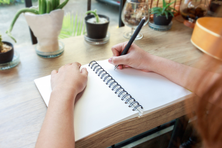 Woman hand writing on notebook paper with a pen on wooden desk in cafe.