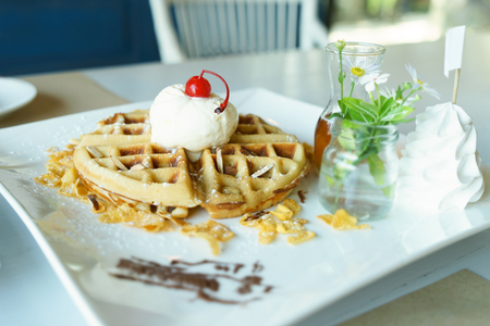 Waffle with vanilla ice cream and honey sauce on white plate