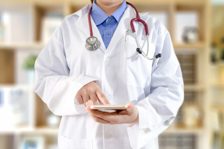 Concept of woman doctor holding and touching screen on smart phone in room