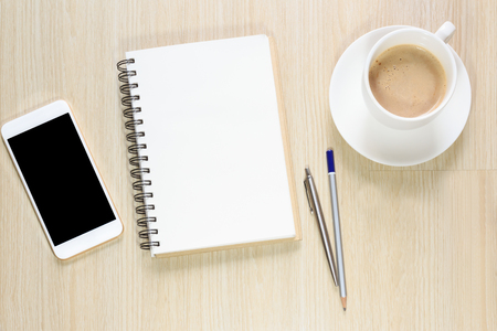 Top view of blank notepad on office desk with smartphone, pen and coffee cup