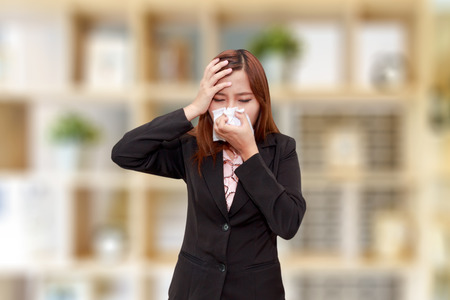 Businesswoman with allergy or cold sneezing into napkin with headache - health concept