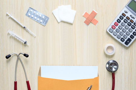 Top view of blank sheet in letter envelope with stethoscope, hypodermic syringe, plaster, gauze, medicine, tape and calculator. Stock Photo