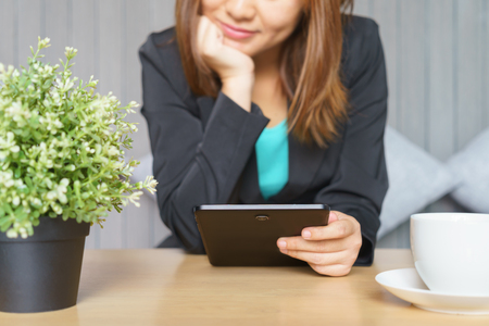 Smile business woman in black suit using tablet at office
