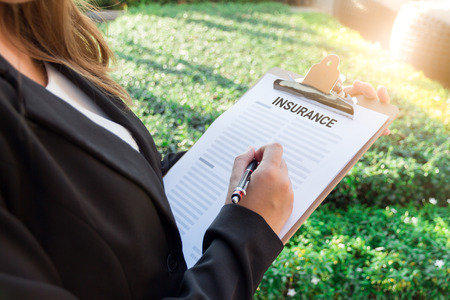 Business women in black suit sign the insurance contract with a pen under sunlight Stock Photo