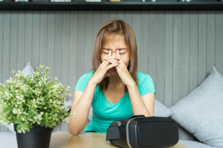 Young woman with virtual reality glasses make her eyes pain. she is rubbing her eyes. Stock Photo