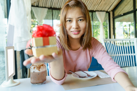 Smile young woman giving a golden present box with red ribbon to her lover in restaurant Stock Photo