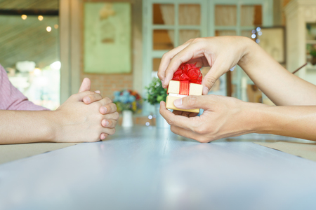 Man hands opening a golden present box with red ribbon to give his lover in restaurant