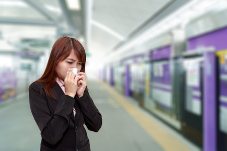 Businesswoman with allergy or cold sneezing into napkin in sky train platform - health concept