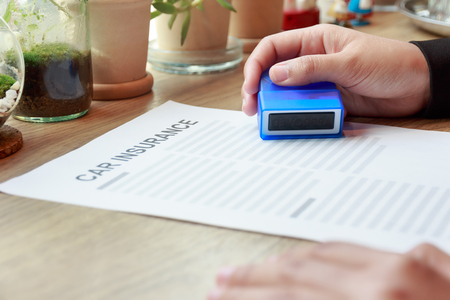 Business woman holding an Approved rubber stamp with car insurance document on wooden desk