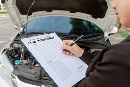 Insurance agent writing on car insurance document and examining car after accident