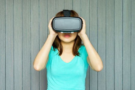 Young woman in virtual reality glasses and holding it with her hands at home Stock Photo