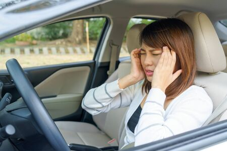 Closeup portrait of young woman touching her temple feels headache in her car after driving car for long time. Stock Photo