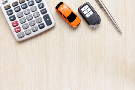 Top view of car key, car toy, pen and calculator on wooden desk. Stock Photo