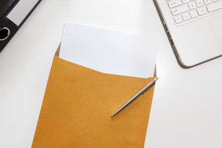 Letter in envelope with file and notebook on desk - business concept. Stock Photo