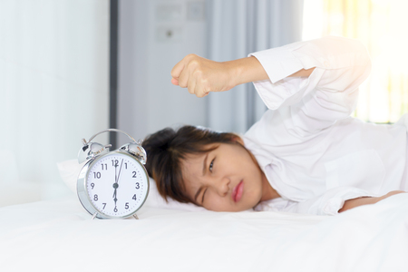 Angry young woman looking at alarm clock with clench ones hand in the morning. early wake up. Stock Photo