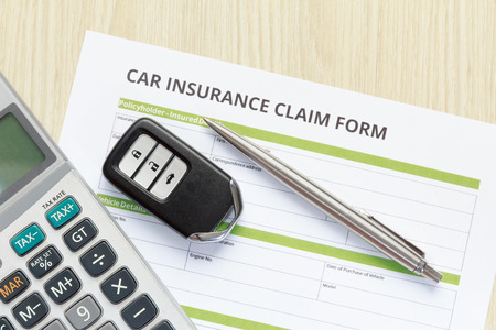 Top view of car insurance claim form with car key and calculator on wooden desk