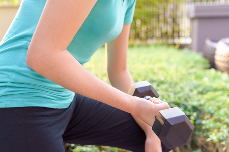 Young woman holding dumbbell for exercising in public park