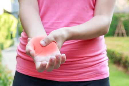 Young woman hands pain in public park concept