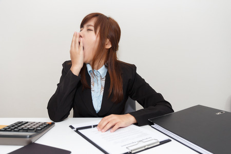 somnolent: Businesswoman yawn or feel sleepy while working at office after having lunch