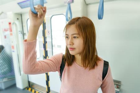 Woman traveler holding the train rails while taking sky train