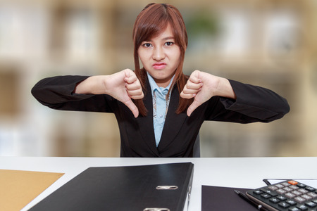 Unhappy business woman with thumb down in office - calculator, file and document on desk Stock Photo