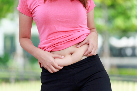 Chubby woman hand holding her own belly fat at outdoor