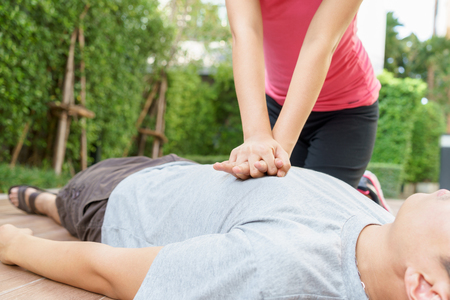 Woman giving cardiopulmonary resuscitation (CPR) to a man at public park