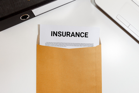 envelope: Insurance document in envelope with file and notebook on desk - business concept.