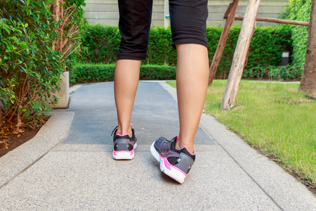 Sporty woman ankle sprain while jogging or running at park