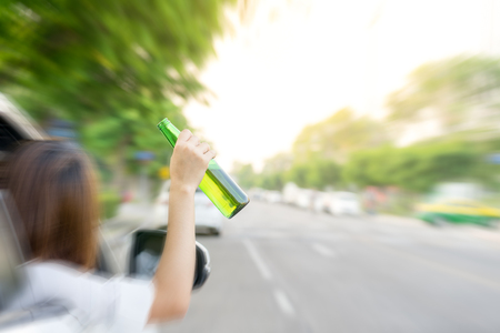 slight: Drunk woman driving and holding beer bottle outside a car